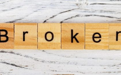 BROKEN word made with wooden tiles set on a timber background